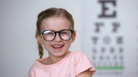 оптический : Joyous little girl in eyeglasses laughing, positive vision treatment results Стоковые видеозаписи