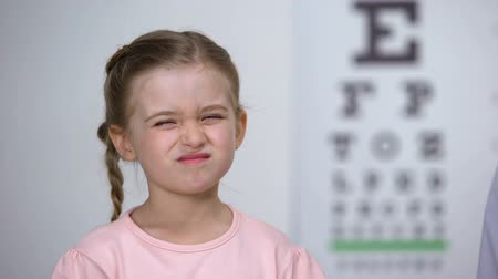 оптический : Optician putting corrective glasses on upset girl, childhood eye diseases Стоковые видеозаписи