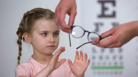 оптический : Upset little girl rejecting glasses, child feels insecure in eyewear, discomfort
