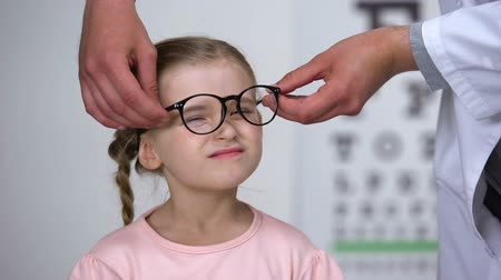 examinar : Optician putting glasses on little girl and making her happy, professional help Stock Footage