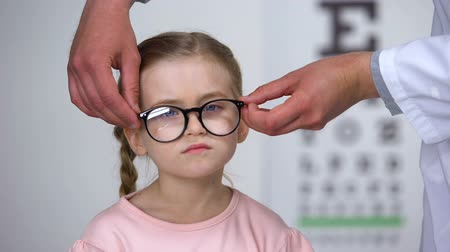 оптический : Capricious little girl rejecting eyeglasses from optician, feels insecure, shy