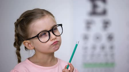 оптический : Pensive smart girl wearing glasses, testing vision with eye chart in clinic Стоковые видеозаписи