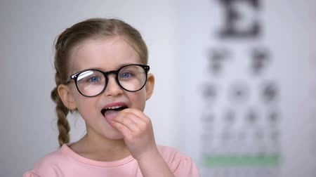 оптический : Cute child girl in glasses taking pills for eyesight treatment, helpful vitamins