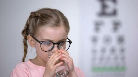 оптический : Beautiful little girl in glasses drinking pill for vision treatment, supplements