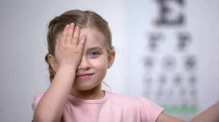 wzrok : Child girl closing eye, showing size or sign from eye chart, vision diagnostics Wideo
