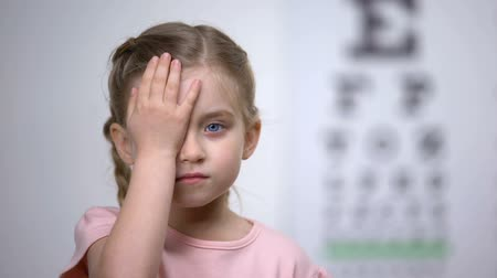 wzrok : Cute child closing one eye to test visual acuity, diagnostics of sight illness