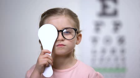 закрытыми глазами : Pretty girl in glasses closing eye, taking vision exam in ophthalmology clinic
