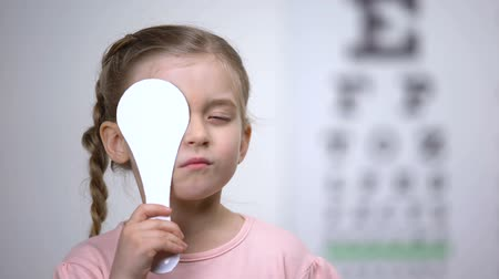 закрытыми глазами : Female preschooler closing eye for complete vision exam, diagnostics of sight