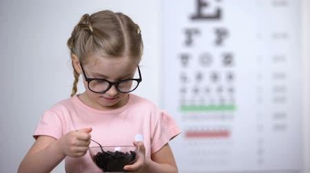 восхищенный : Smiling girl in glasses eating blueberries, natural vitamins to improve vision Стоковые видеозаписи