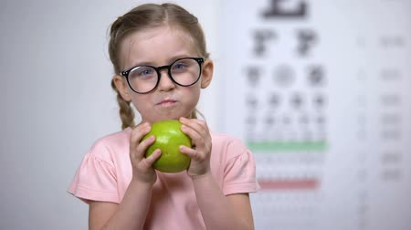 ajánlás : Adorable girl in glasses eating apple, natural vitamins for eyes, healthcare Stock mozgókép
