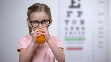 alimentos naturales : Positive little girl drinking carrot smoothie, healthy nutrition, eye vitamins Archivo de Video