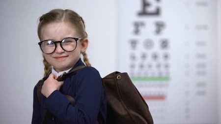 diagnostics : Pretty schoolgirl in glasses smile, awareness of complete eye exam before school Stock Footage