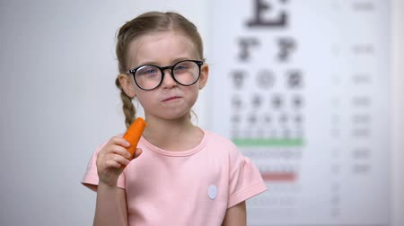 delighted : Happy cute girl in eyeglasses eating carrot, vitamin A for good vision, health