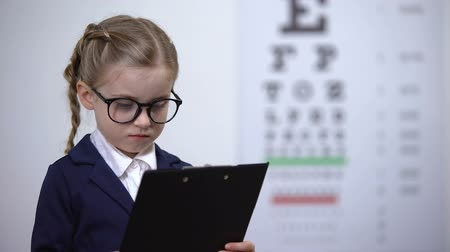 optyk : Adorable child girl pretending to be eye doctor, future profession optometrist