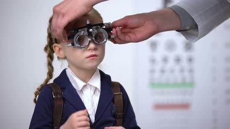 phoropter : Optometrist putting optical trial frame on schoolgirl to determine visual acuity Stock Footage