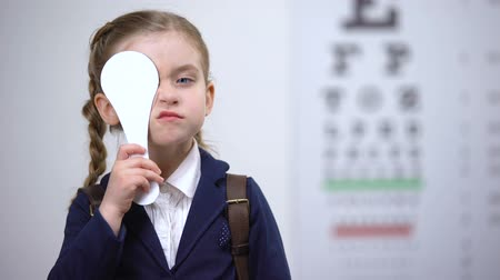 cornée : Schoolgirl closing one eye for complete vision exam, diagnostics of sight