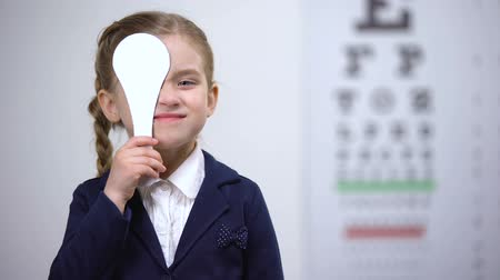 закрытыми глазами : Cheerful schoolgirl closing eye, checking vision in ophthalmological clinic Стоковые видеозаписи