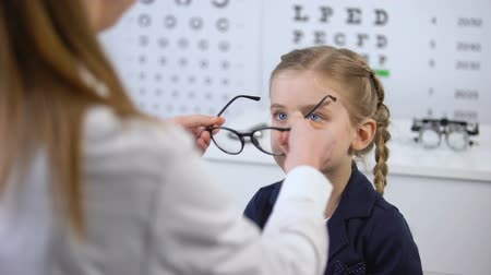 оптический : Optician putting glasses on schoolgirl, little client happy with stylish eyewear