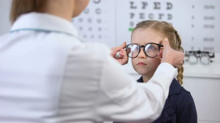 оптический : Female doctor putting glasses on disgruntled girl, child feels insecure, upset
