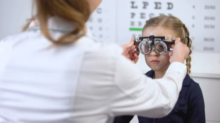 soczewki kontaktowe : Pretty little schoolgirl visiting oculist for measuring eyesight with phoropter