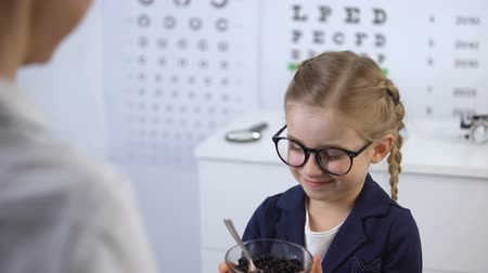 оптический : Ophthalmologist giving blueberries to cute little girl, natural vitamin for eyes Стоковые видеозаписи