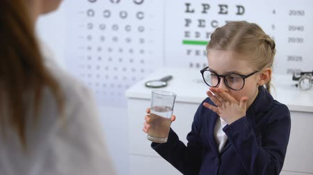 tomar : Optician giving pills to little girl, eye disease treatment, vision vitamins