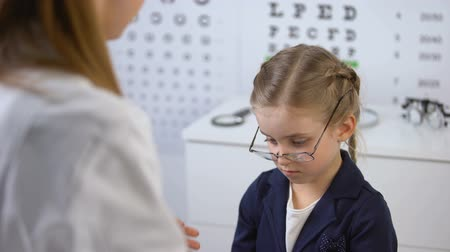 оптический : Kind optician supporting schoolgirl with broken eyeglasses, victim of bullying