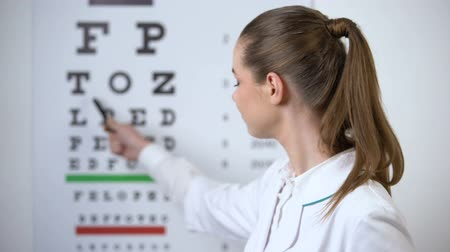 оптический : Female optometrist pointing at eye chart, vision test in ophthalmology clinic Стоковые видеозаписи
