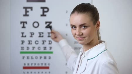 clínico : Professional female optician pointing at eye chart, timely diagnosis of vision