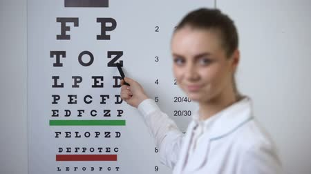 оптический : POV patient focusing sight on eye chart, doctor confirms successful vision exam