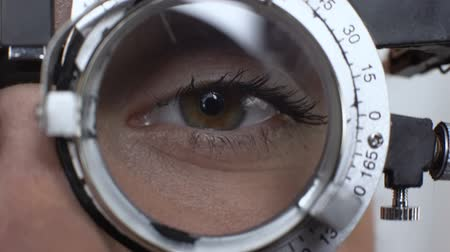 оптический : Woman eye with changed lens in phoropter, visual acuity test, cornea diagnostics Стоковые видеозаписи