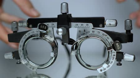 phoropter : Hands putting optical trial frame on table, ophthalmic testing device close-up