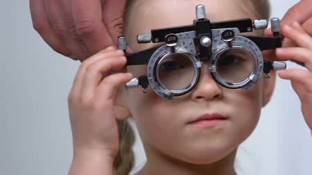 phoropter : Ophthalmologist helping small girl put on phoropter, eyesight checkup diagnostic