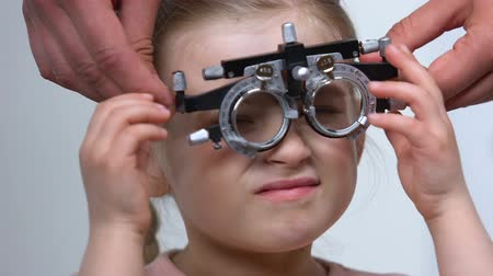 phoropter : Female child squinting eyes wearing optical trial frame, eye examination, myopia Stock Footage