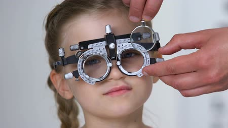 phoropter : Optometrist choosing lens for child patient using phoropter, clinic consultation