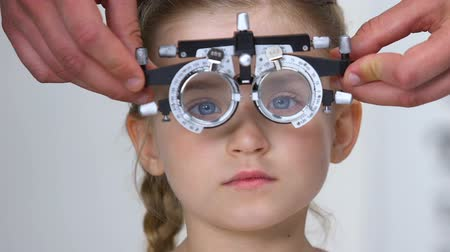 phoropter : Pretty female kid in optical trial frame, optometrist choosing proper lens