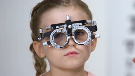 miopia : Male ophthalmologist choosing eyeglasses lens for small girl wearing phoropter