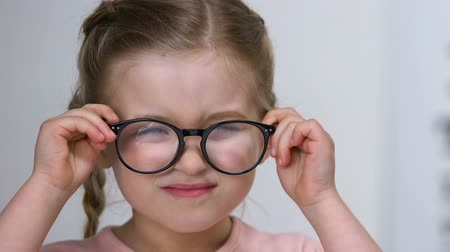 nearsightedness : Small kid squinting eyes putting on eyeglasses and smiling, farsightedness