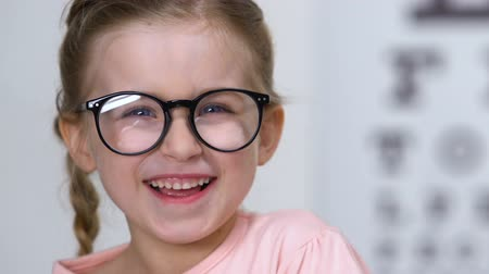 optometria : Joyful little girl in eyeglasses laughing on camera, ophthalmology and health