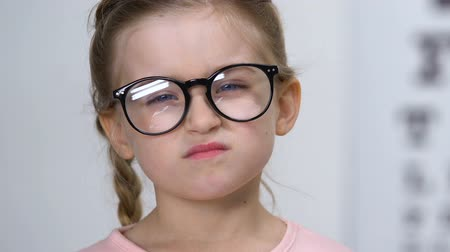 shy girl : Upset small female kid taking off eyeglasses, childhood insecurities, myopia