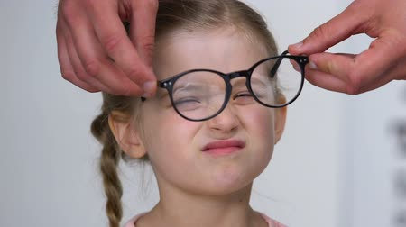 nearsightedness : Male ophthalmologist giving eyeglasses to small farsighted girl, health care Stock Footage