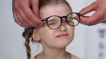 nearsightedness : Female kid putting on eyeglasses and smiling, optometrist consultation, close-up