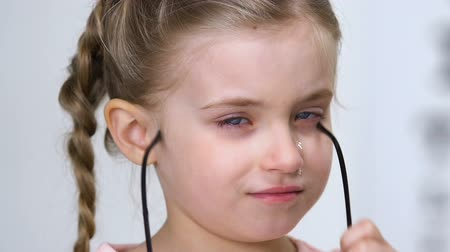 nearsightedness : Crying female kid taking off eyeglasses, child bullying, insecurities concept