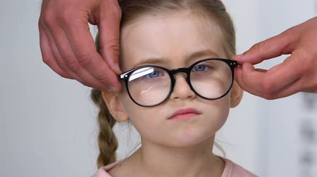 nearsightedness : Caucasian girl squinting eyes taking off eyeglasses, lens choice, prescription Stock Footage