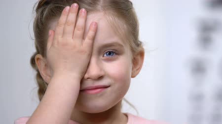 nearsightedness : Cute happy schoolgirl covering eye with hand, medical consultation ophthalmology Stock Footage
