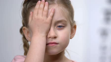 nearsightedness : Female child covering eye with hand, ophthalmological exam, nearsightedness