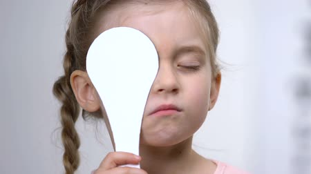 nearsightedness : Cute girl covering eye, vision check in clinic, ophthalmological test, eyesight Stock Footage