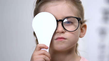 nearsightedness : Pretty female child in eyeglasses covering eye examination tool, medical test Stock Footage