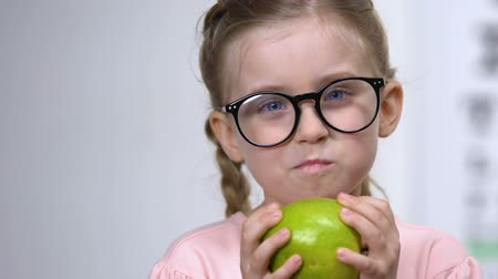 nearsightedness : Smiling little girl eyeglasses eating green apple, healthy nutrition, vitamins Stock Footage