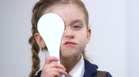 nearsightedness : Small girl covering eye during eyesight examination, school vision test, optics